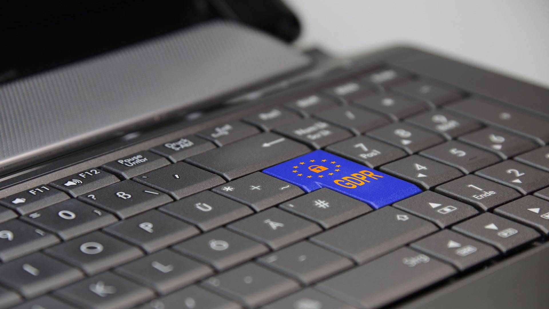 Computer keyboard with a blue key displaying GDPR in yellow gold