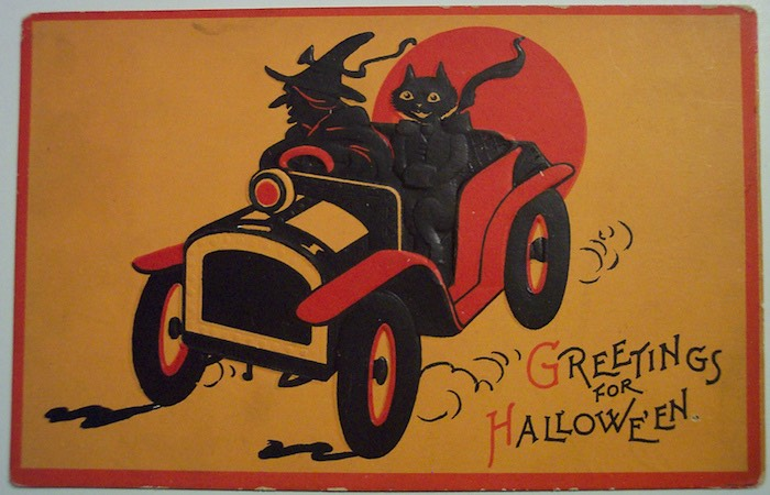 Vintage graphic of an old car with a black cat in it, text displaying Greetings for Halloween