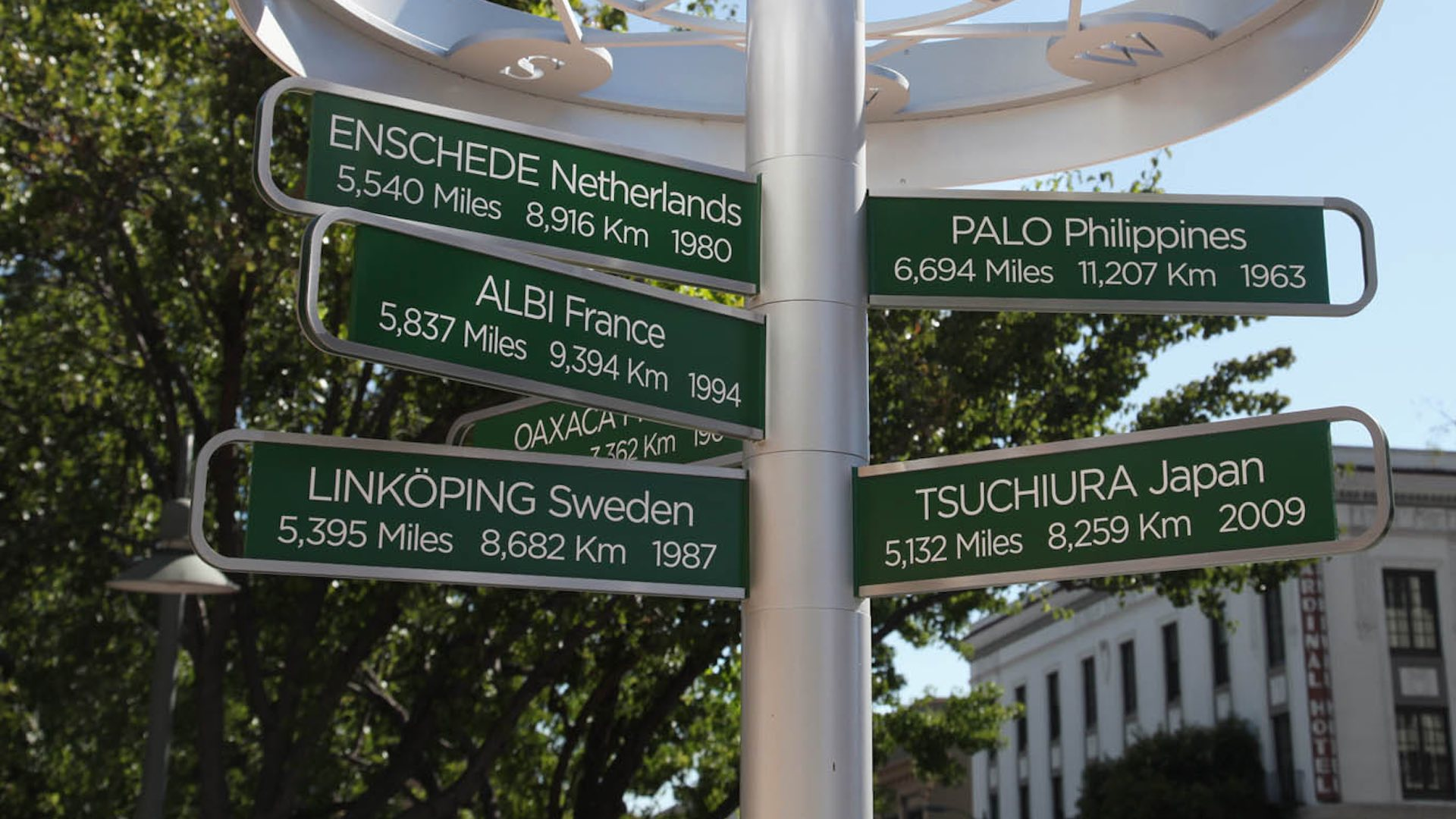 Aluminium fixture outside of City Hall displaying signs with directions and distances to various cities in the world, with the Cardinal Hotel in the background