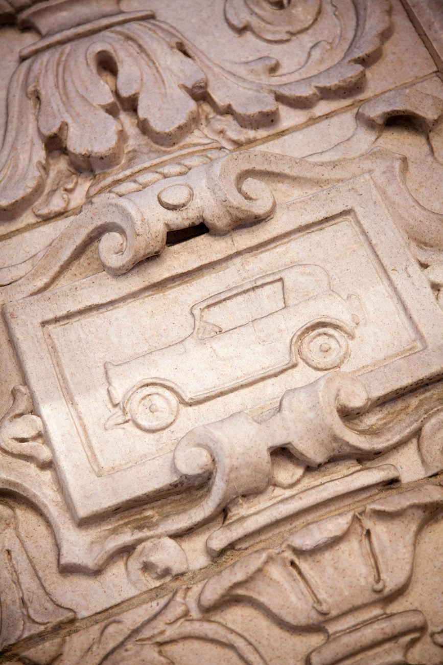Detail outside view of a vintage car engraved in the wall surrounding the main entrance of the Cardinal Hotel