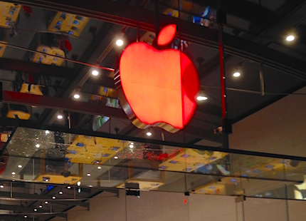 Big red apple hanging from the ceiling of an apple store