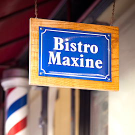 Bistro Maxine logo on a street sign at the entrance of the restaurant