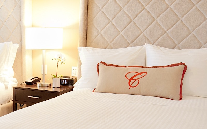 Guest room bed with pillow displaying the big C of the Cardinal Logo