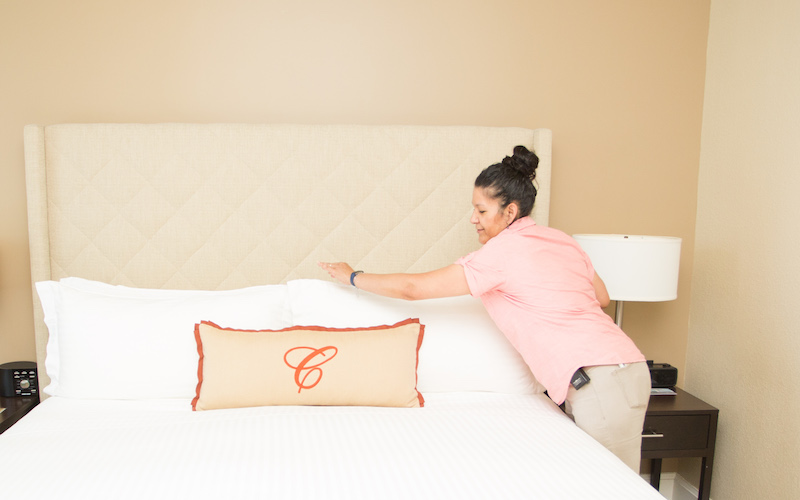 Housekeeper arranging a pillow on a bed