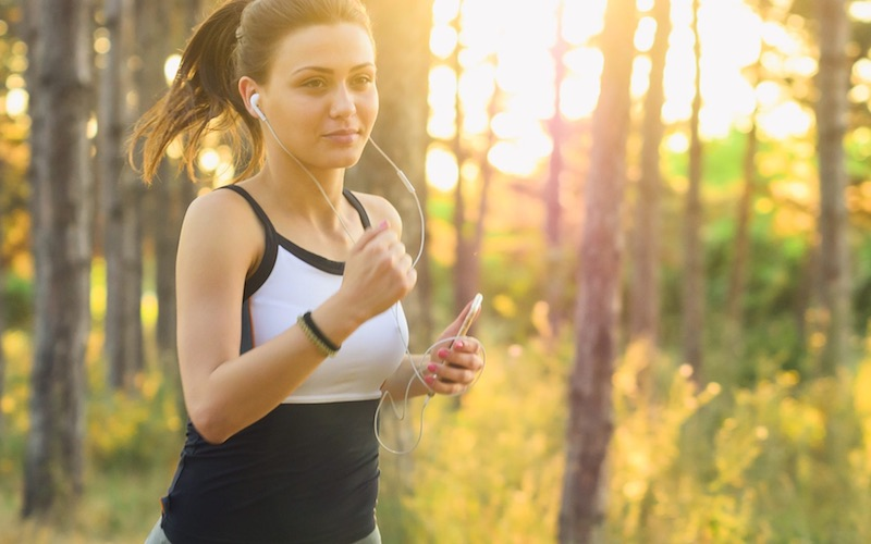 Woman jogging in the forest with headphones