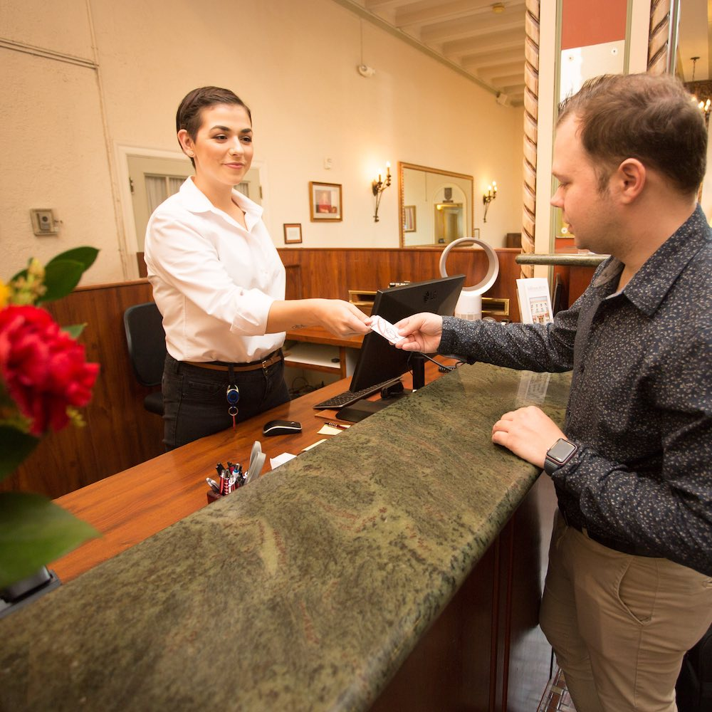 Front desk staff handing out a room key to a guest