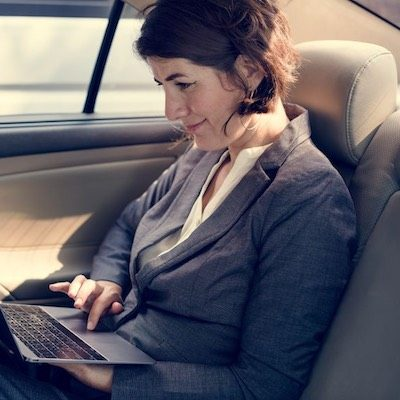 businesswoman working using laptop car inside