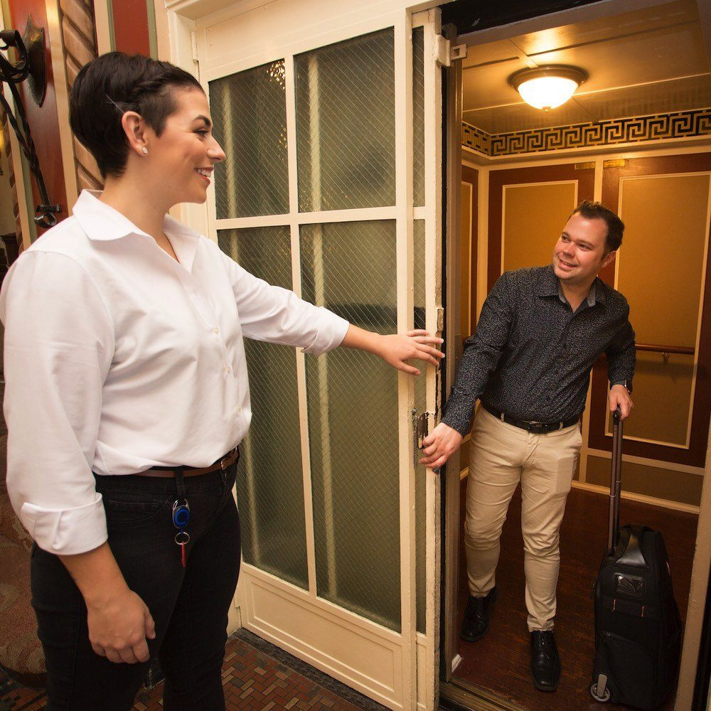 Front desk customer service representative holding the elevator door for a guest
